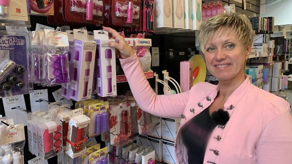 Sexleksaker på en vägg. Framför står en kvinna i rosa kavaj.