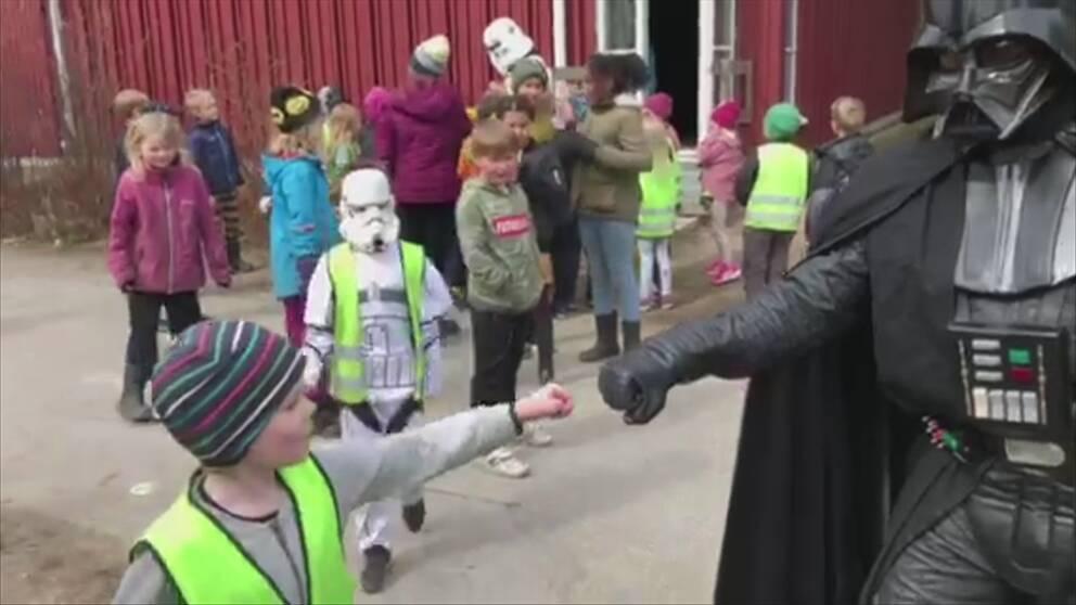En liten pojke och en person utklädd till Darth Vader håller dina knutna nävar mot varandra. I bakgrunden syns flera barn, varav en har en vit mask på sig.