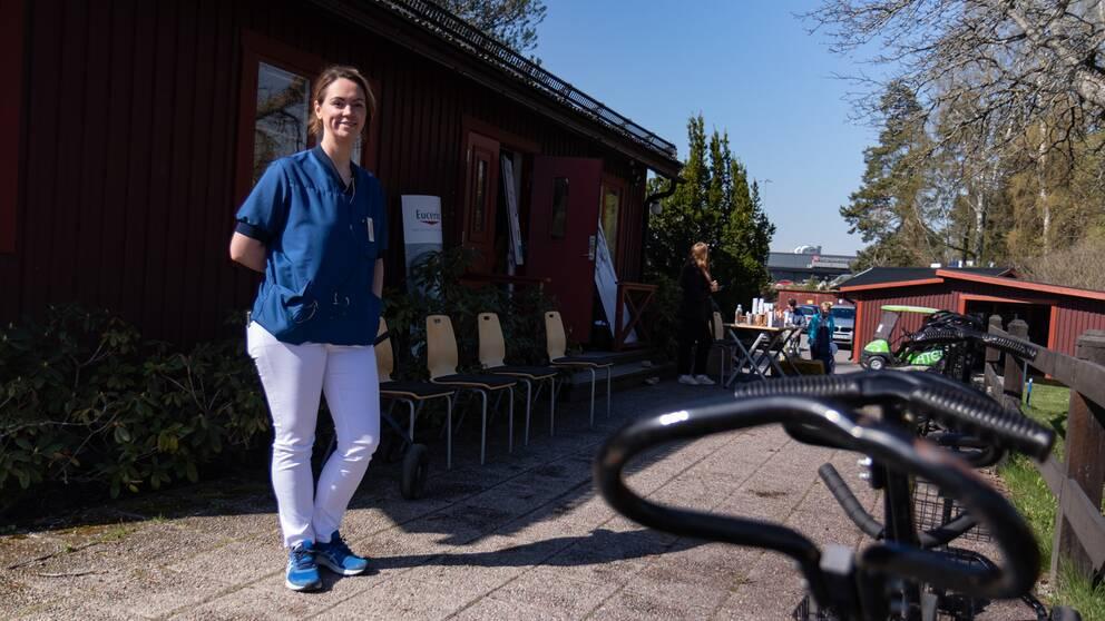 en kvinna i läkarblus och vita byxor på en uteplats på golfklubben i Gävle