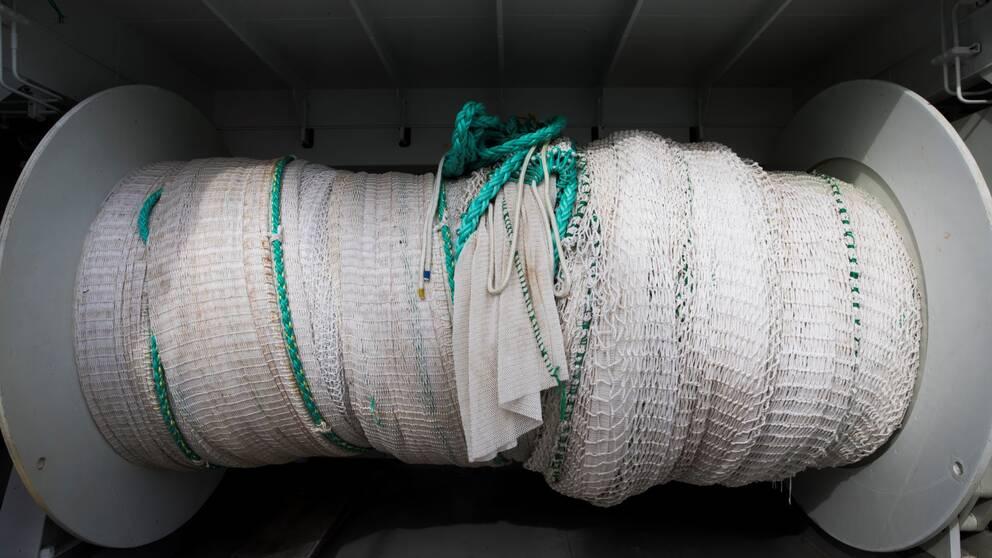 Närbild på en hoprullad trål på en fiskebåt.