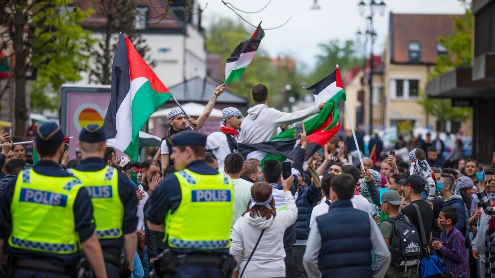Demonstration på Stortorget i Växjö. Några av demonstranterna har palestinasjalar på huvudet och håller i den palestinska flaggan. Tre poliser står med ryggarna mot kameran.