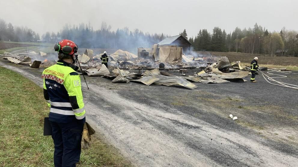 räddningspersonal tittar på resterna av en byggnad, det ryker