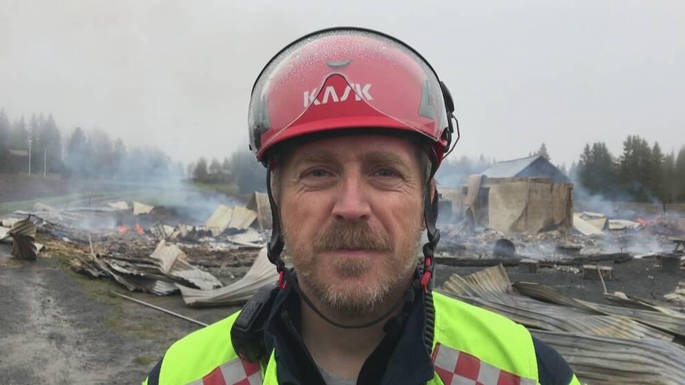 närbild på man i hjälm räddningstjänstens jacka, framför rykande rester av en brand i byggnad