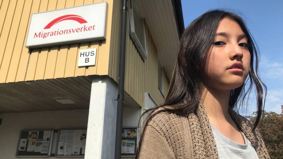 """En tjej med mörkt hår står framför ett gult hur. På huset finns det en skylt med texten """"Migrationsverket""""."""