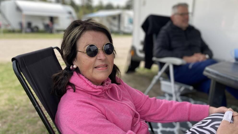 en medlelålders kvinna i solglasögon och rosa luvtröja sitter i en campingstol utanför husvagn