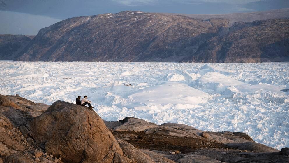 Två forskare vid glaciären Helheim i Grönland.