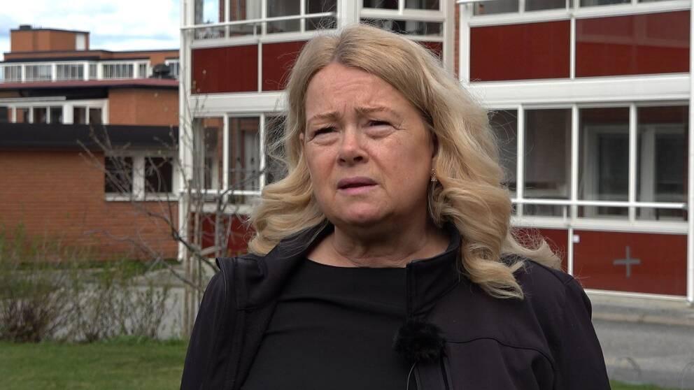 Kvinna med långt blont hår och svarta kläder.