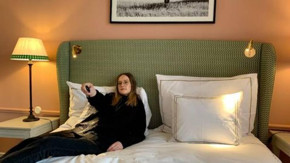 Reporter lutar sig tillbaka i hotellsängen och håller en fjärrkontroll i handen. Till vänster i bild syns en lampa, väggarna är i persikofärg och över sängen hänger en tavla.