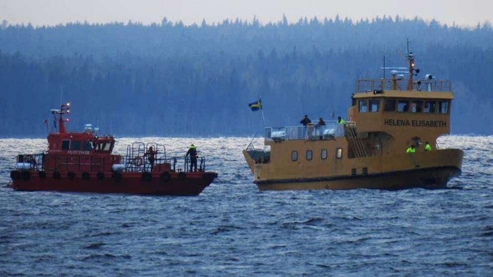 En röd lotsbåt och en gul passagerarfärja på ett vågigt hav i skymningen.