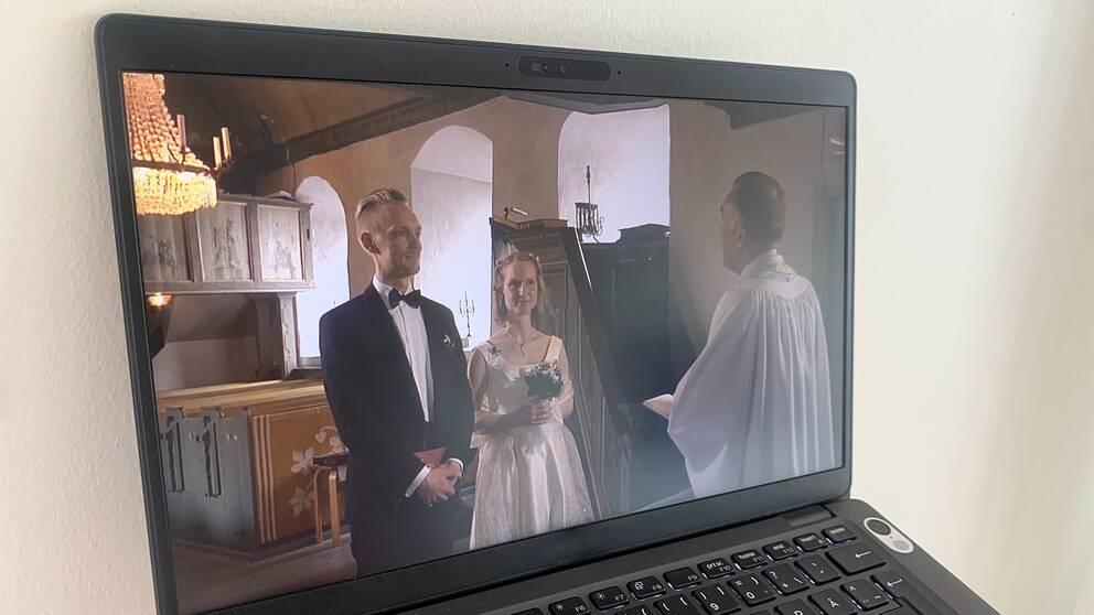 På en datorskärm syns en brudgum och brud i en kyrka framför en präst.