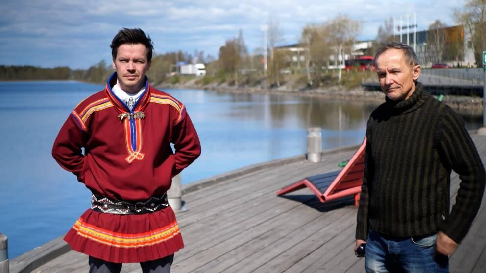 en man i samisk kolt och en något äldre man i stickad tröja står på en träbrygga i stad