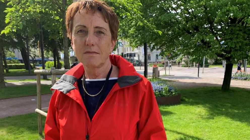Kortklippt kvinna med röd jacka tittar in i kameran.