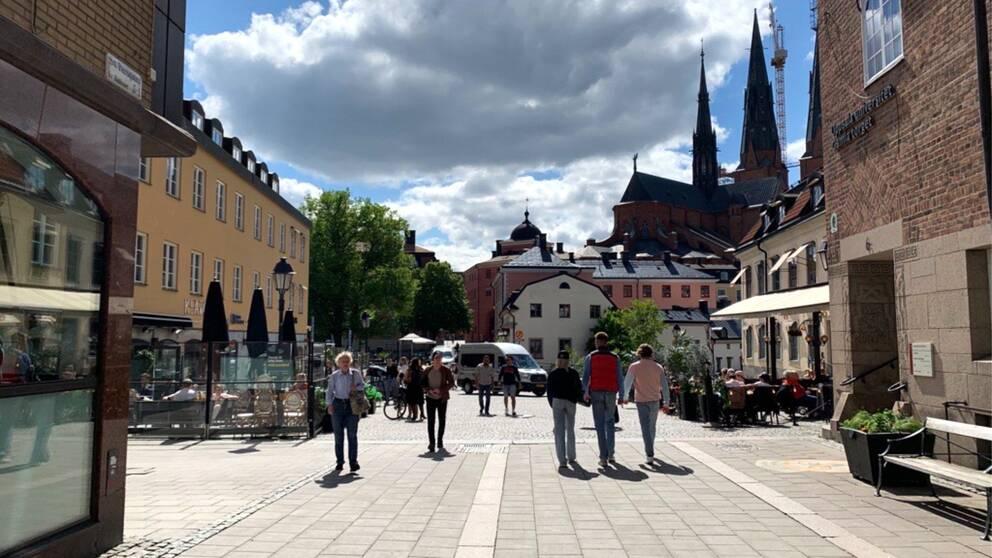 Personer går eller sitter vid uteserveringar på Gamla torget i Uppsala.