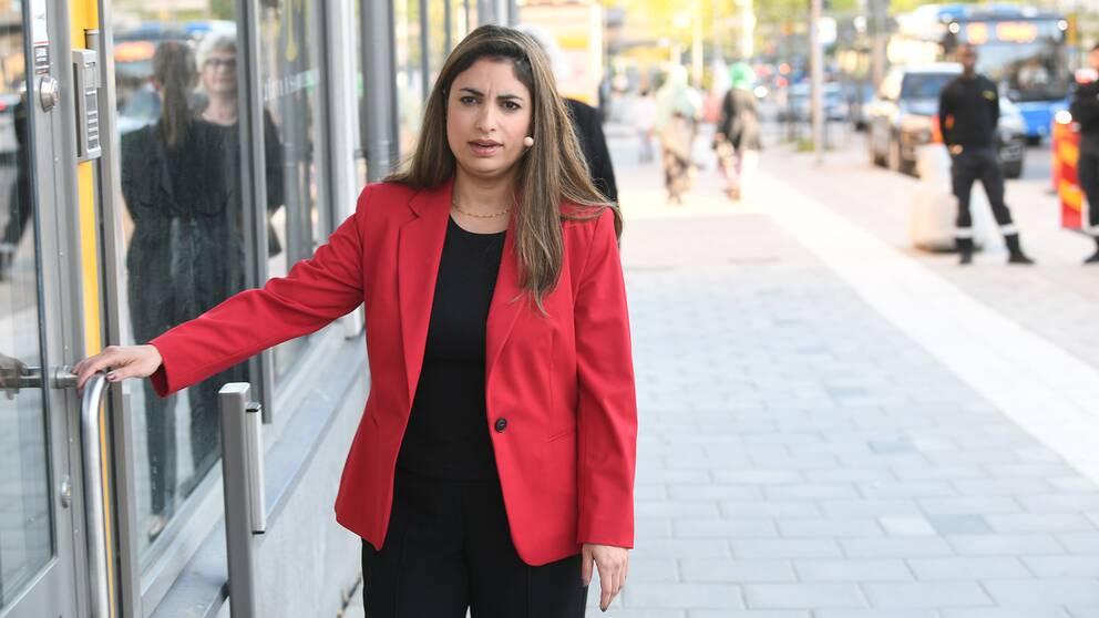en kvinna i röd kavaj på väg in i en byggnad, har headset-miokrofon vid kinden
