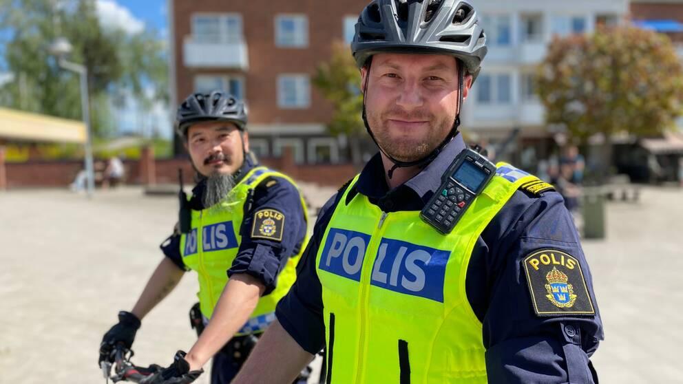 närbild två manliga poliser i cykelhjälm på ett torg