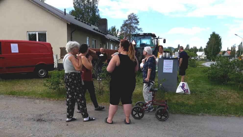 Personer står samlade vid ett hus