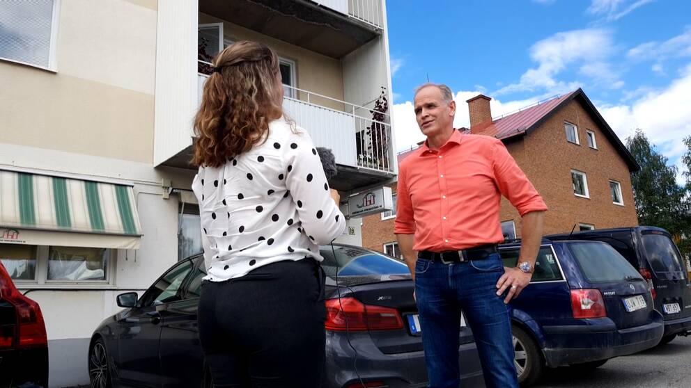 Gråhårig man i laxrosa skjorta står framför en kvinna med mörkt lockigt hår och vid blus med svarta prickar.