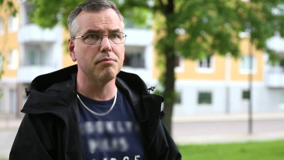 En bild på en man som står utomhus i ett bostadsområde.