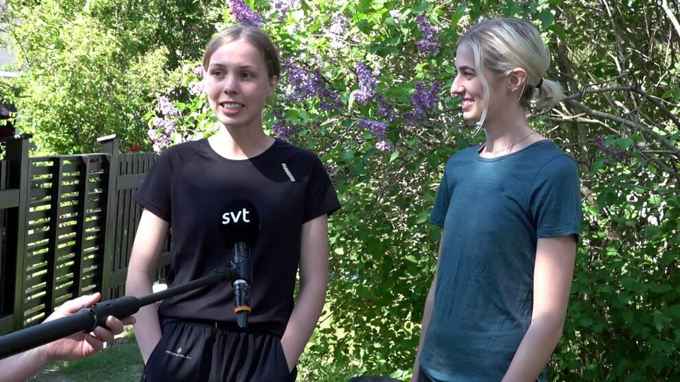 Två unga tjejer intervjuas av SVT framför en syrénbuske i solsken