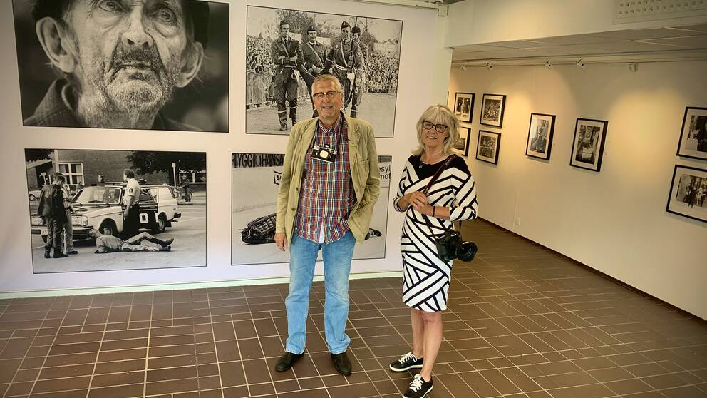 man och kvinna i utställningshall med svartvita foton på väggarna
