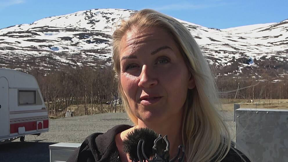 kvinna som intervjuas med snöfläckiga fjäll i bakgrunden, husvagn skymtar