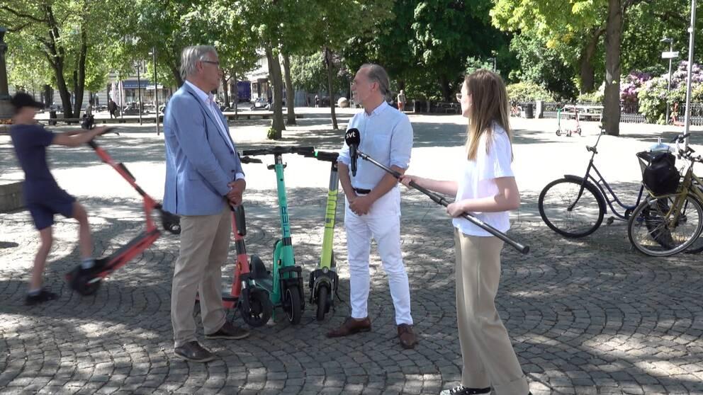 Från vänster i bild åker en person på bakhjulet på en elsparkcykel bakom politikerna Jan Valeskog och Daniel Helldén. Politikerna står framför tre elsparkcyklar från tre olika företag. Det är soligt och träd syns i bakgrunden. Lite till höger om politikerna står reportern med en mikrofon på en lång pinne.