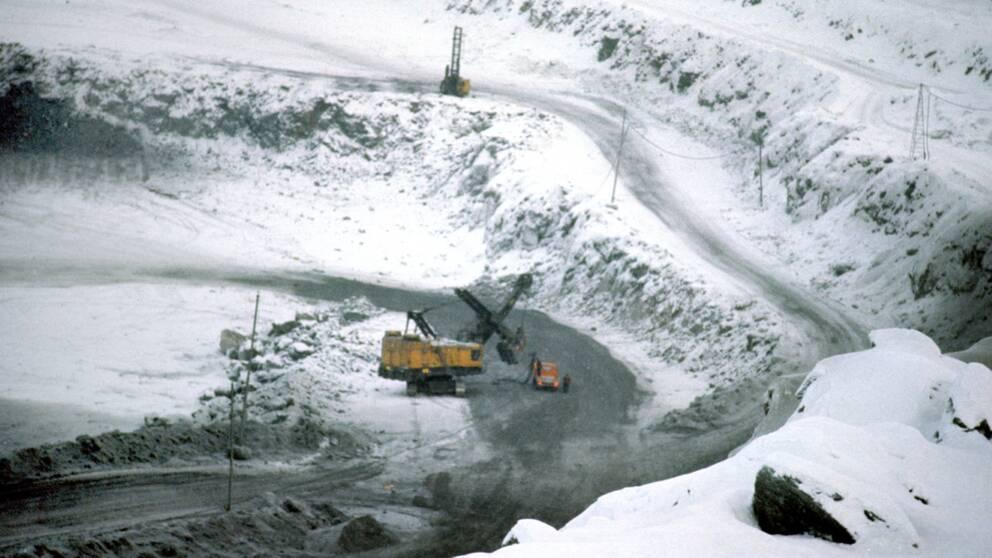 en gruvmaskin, en bil och en människa syns nere i en jättelik grusgrop med en väg ner, tunt snötäcke
