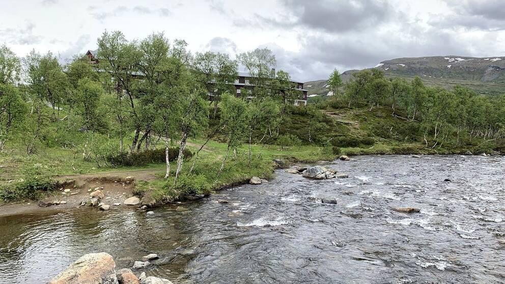 vy över vattendrag, gles björkskog, fjäll och den stora turiststationen som skymtar