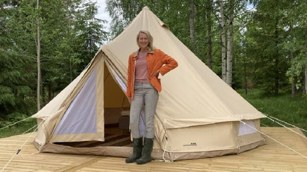 en kvinna står framför ett tält på ett trädäck med skog i bakgrunden