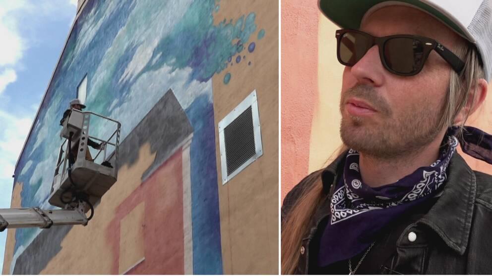 Till vänster en skylift med en konstnär som håller på att göra en muralmålning på en husvägg. Till höger en man med svarta glasögon och vit keps.