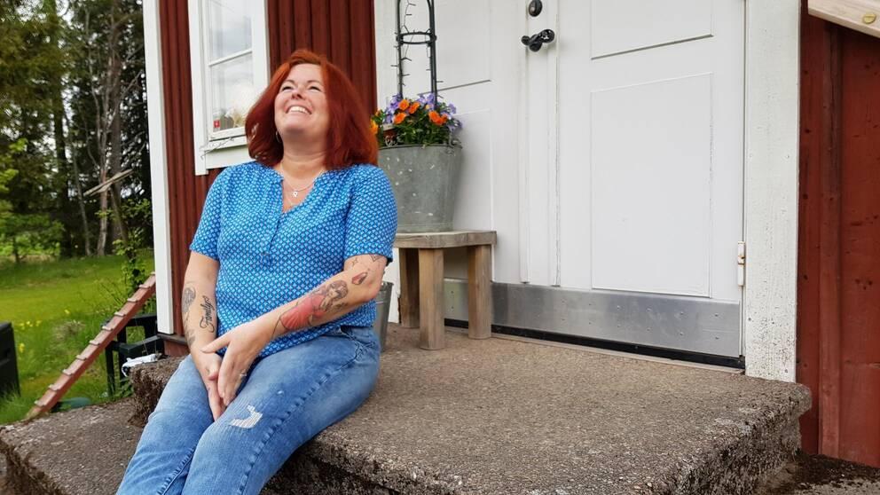 Kvinna i blå¨blus som sitter på en trapp. Hon tittar uppåt och skrattar.