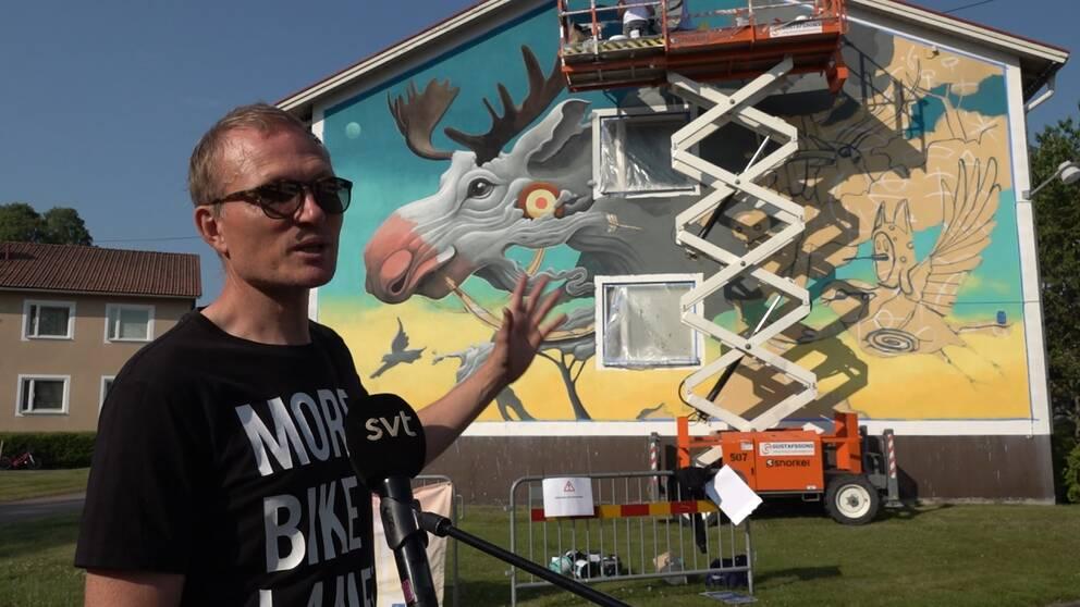 Albin Wiberg, projektledare, framför spanska konstnären Dulks målning på ett hyreshus i lilla samhället Hjorted.