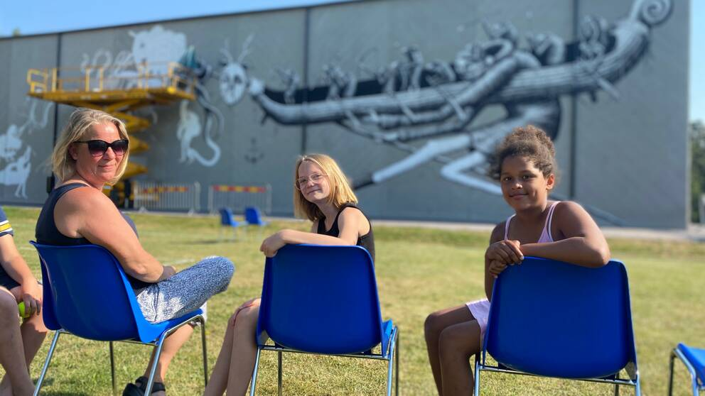 Tre personer, en kvinna och två unga flickor sitter på varsin blå plaststol framför en väggmålning. De tittar in i kameran.