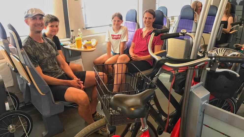 Familjen Woodworth sitter på tåget, med sina cyklar.