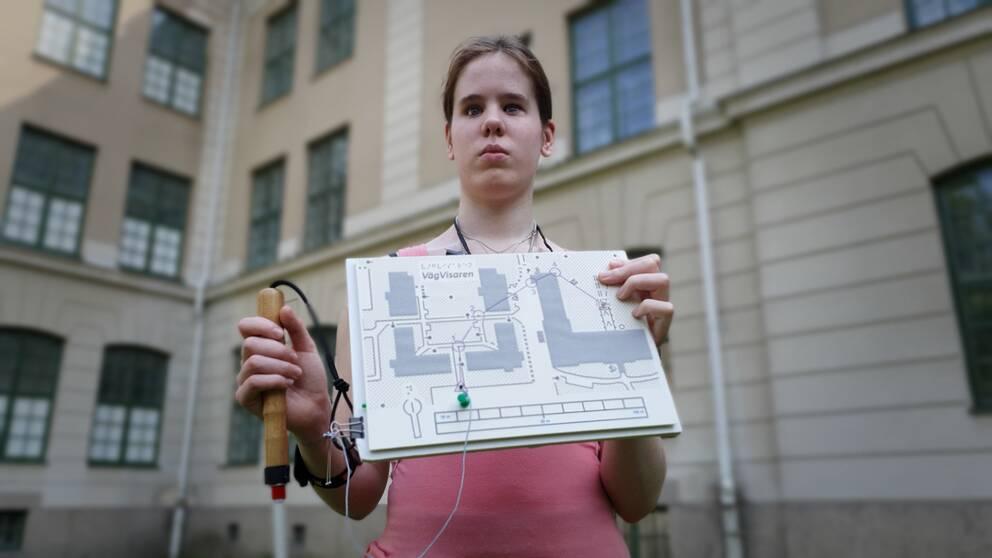Felicia Nordström håller fram en taktil karta över området Västerpark i Örebro.