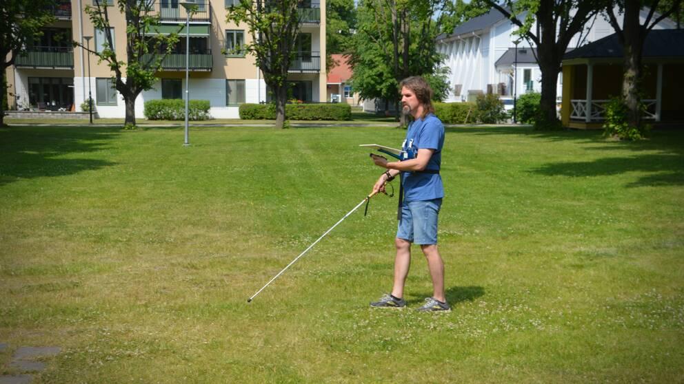 Fredrik Stockhaus orienterar på en stor gräsyta i en park.