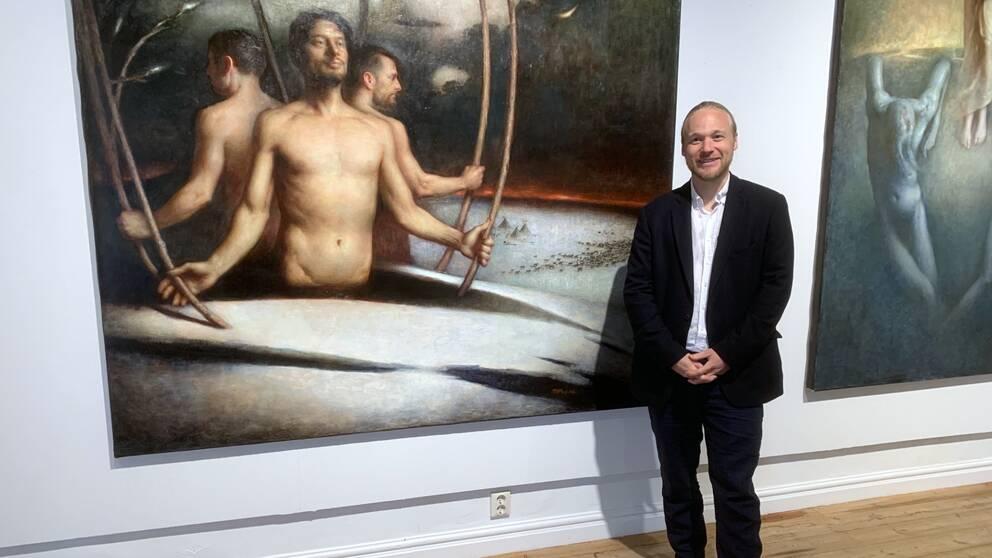 Per Elof Nilsson Ricklund framför ett par av sina oljemålningar.