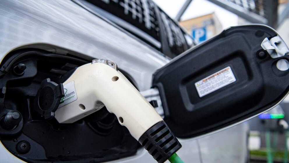 närbild: handtag till elbils-laddare sitter i uttaget på bil