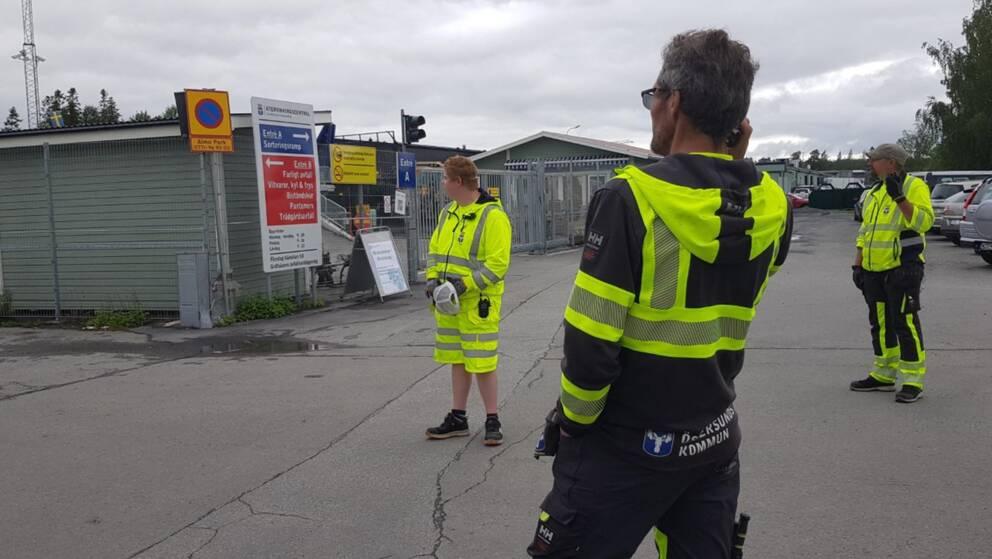 Tre män i arbetskläder utanför en återvinningsstation.