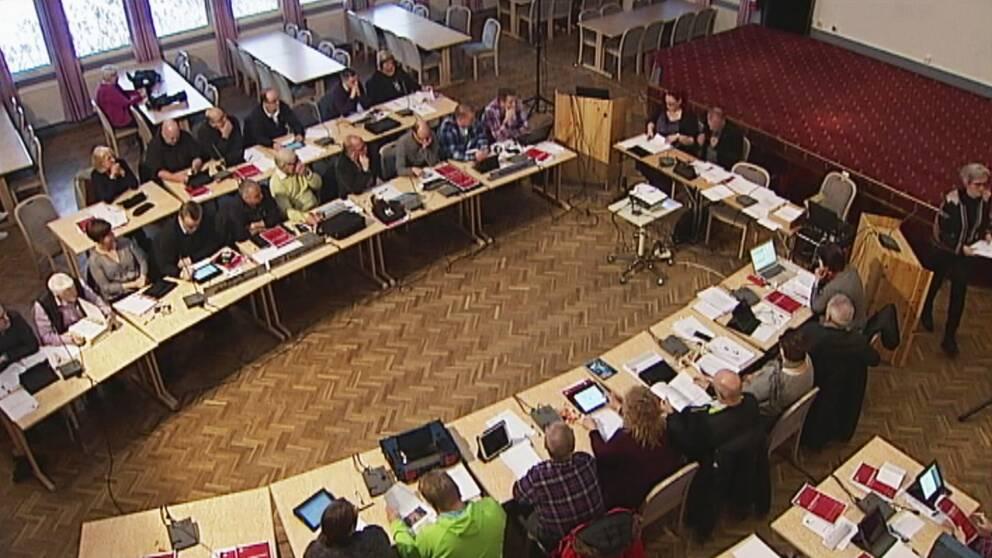 Massvis av människor som sitter runt två avlånga bord med datorer och papper framför sig. Det är ett kommunfullmäktige-möte i Övertorneå.