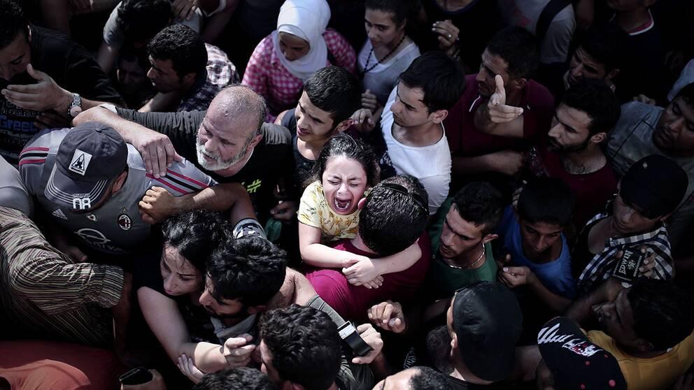 Ett barn gråter i kön till att registrera sig på en stadion på ön Kos.