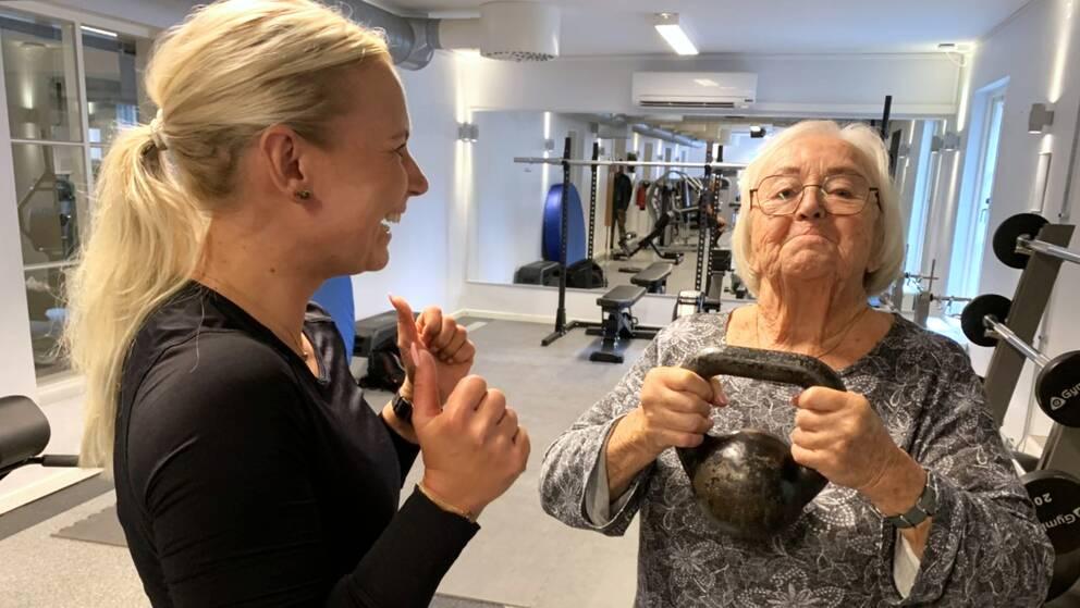 88-åriga Inga-Lill Johansson från Varberg lyfter en kettlebell under uppsyn av sin personliga tränare Carolina Enberg.