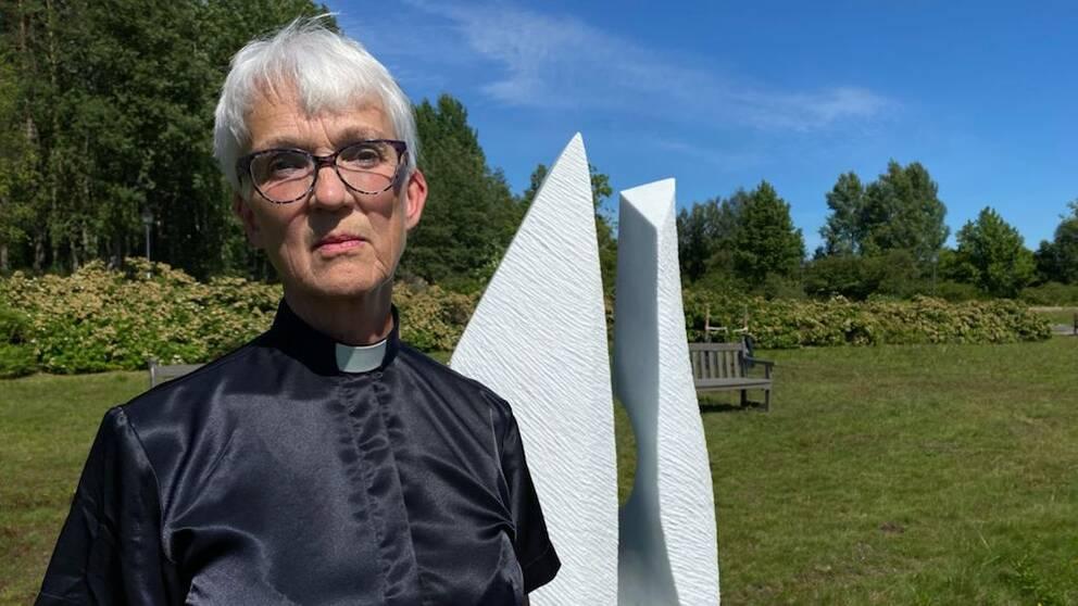 En kvinna i glansig prästskjorta står framför en vit skulptur i en grönskande park.