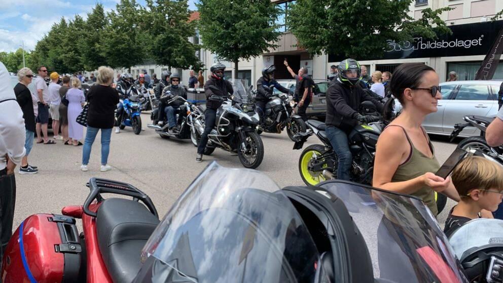 På bilden syns motorcykel-kortegen och en del av de människor som samlats för att se den.