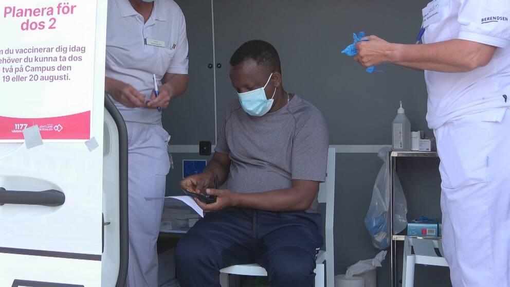En man sitter på en stol och bär munskydd och grå t-shirt väntar på att få sitt vaccin. En sköterska klädd i vitt till vänster och en sköterska klädd i vitt till höger om mannen.