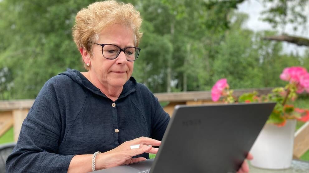Bild på en kvinna i 60-årsåldern som sitter framför en svart laptop. Hon sitter utomhus på en veranda, i bakgrunden skymtar grönska.