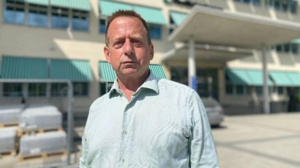 Niklas Löfgren står framför försäkringskassan kontor. Bakgrunden är suddig. Löfgren har en ljus skjorta på sig.