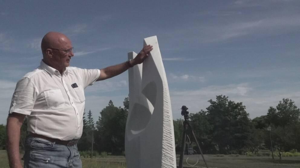 En man håller sin hand mot en marmorskulptur.