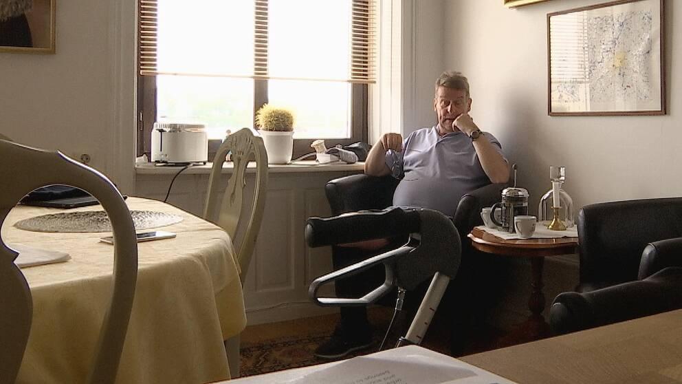 en man sitter i hörnet hemma i lägenheten, rollator-handtag i förgrunden