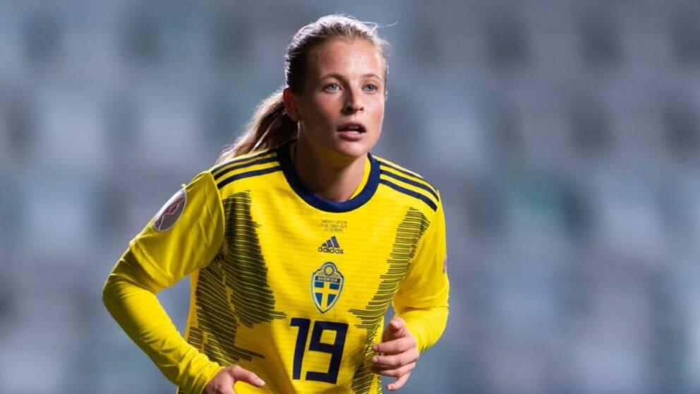 Blond tjej i gul landslagströja på fotbollsplan